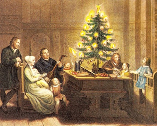 Families Worshipping Christ As They Gather Around A Candle Lit Tree